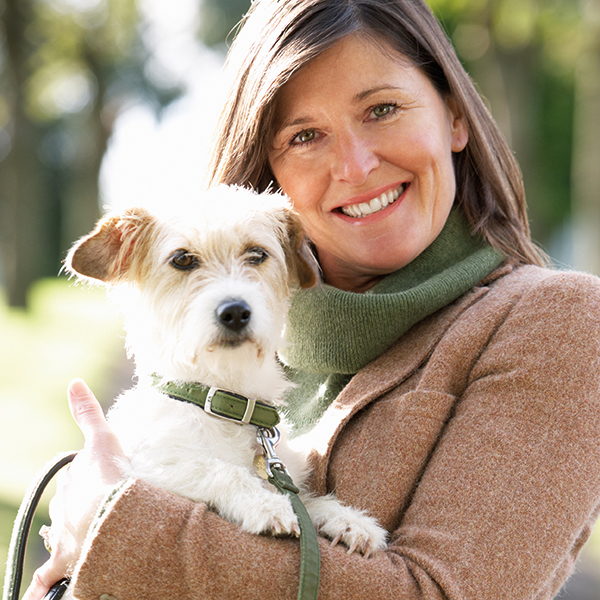 Woman Walking Dog Outdoors In Autumn Park Pic: Istockphoto