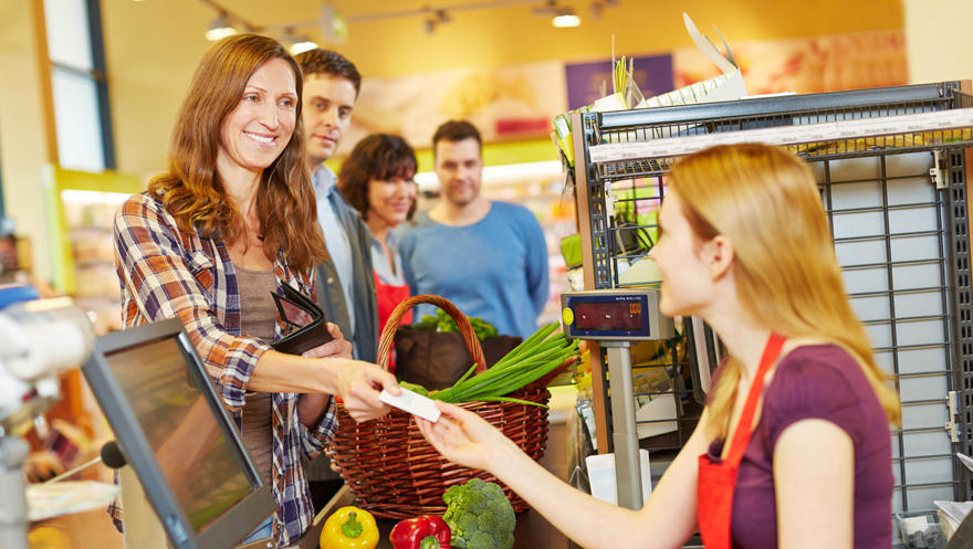 Lady smiling at supermarket checkout Pic: Rex/Shutterstock