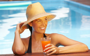 Lady relaxing in a swimming pool abroad Pic: Rex/Shutterstock