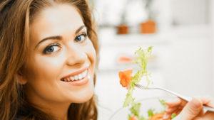 A happy woman eating salad. A healthy diet is key in managing diabetes
