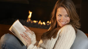 Woman reading in front of fire at home sat on sofa Pic: Istockphoto