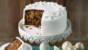 A Christmas cake decorated with fondant icing snowflakes on a stand, a generous slice cut