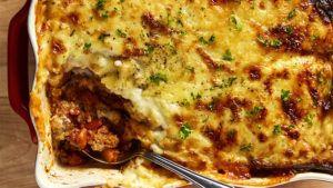 A freshly cooked dish of gluten free lasagne, one portion removed