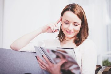 Attractive happy brown haired girl relaxing on couch and reading a magazine