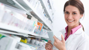 A smiling female pharmacist reading medicine bottle in pharmacy