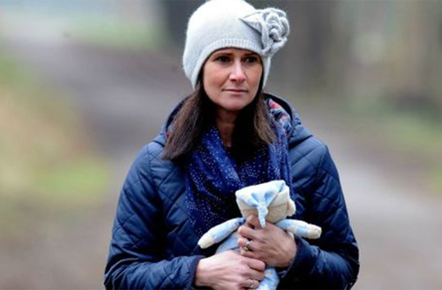 Rhian Burke, outdoors, looking pensive and holding a cuddly toy
