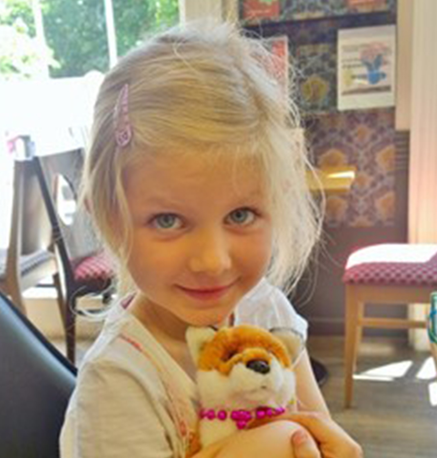 Natalia's daughter Elizabeth, a happy blonde 5-year-old girl cuddling a soft toy