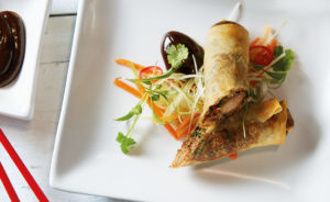 Duck spring rolls arranged with shredded vegetables, dish of hoi sin sauce and red chopsticks