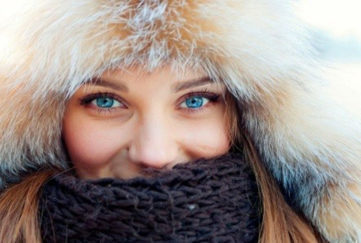 Smiling woman with bright blue eyes in furry hat and woollen scarf