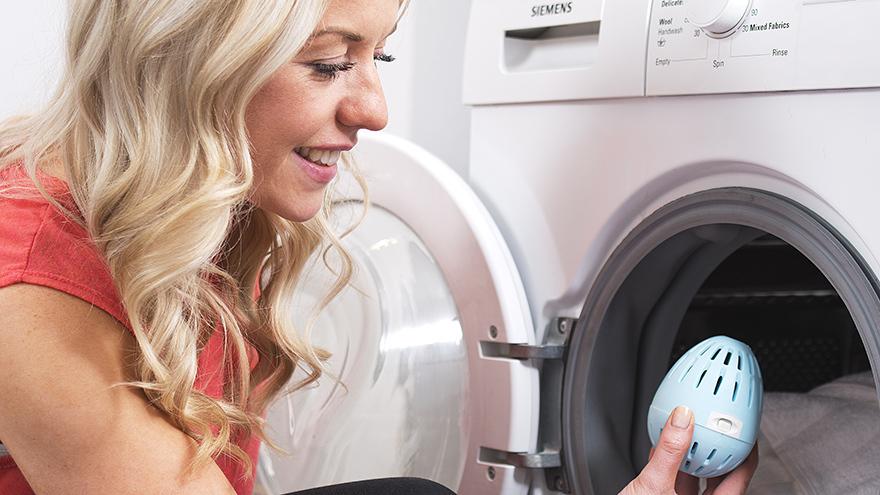 Lady putting laundry egg in washing machine
