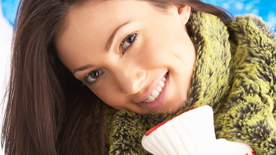 Smiling woman dressed warmly hugging hot water bottle