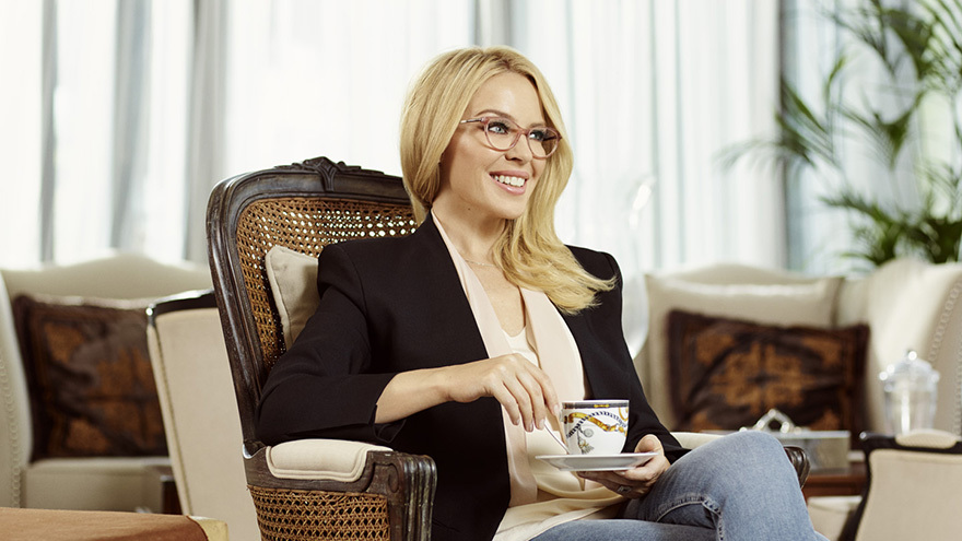 Kylie drinking tea wearing glasses