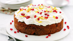 Passion cake with orange zest and pomegranate seeds on frosting