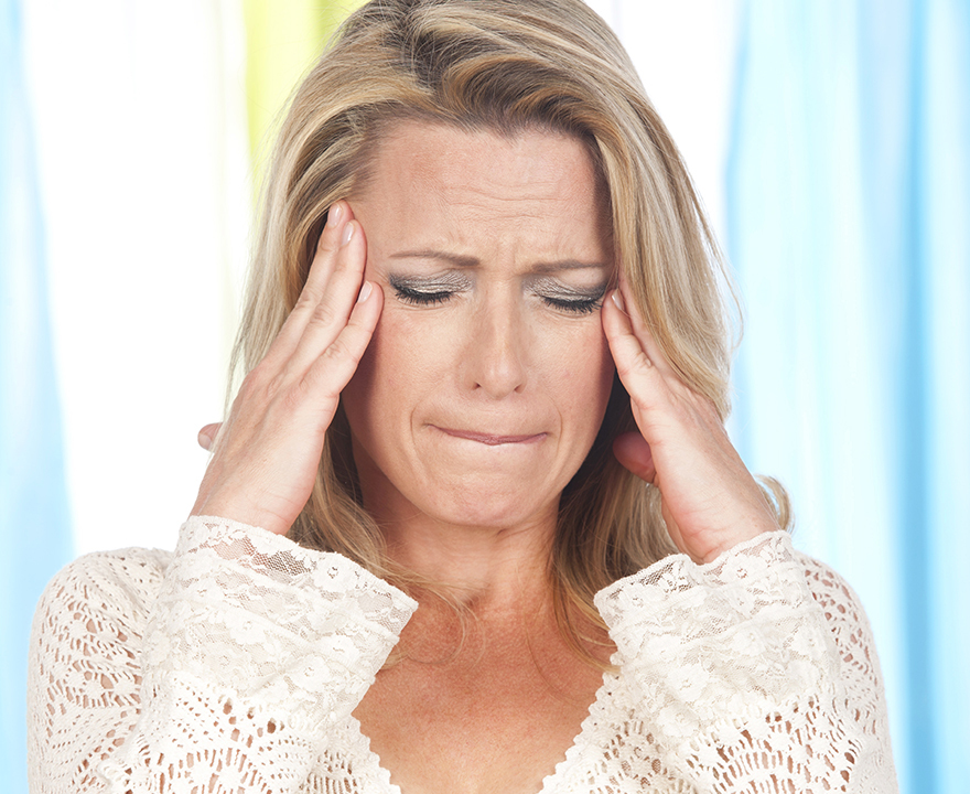 Mature woman with hands to her temples, feeling dizzy
