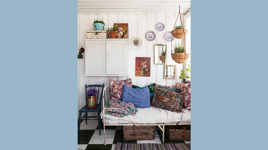 Interior of a decorated shed with painted walls, cushions, plants etc