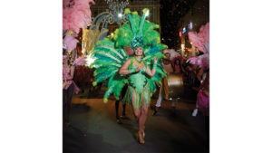 Lady in exotic green outfit dancing at an outdoor carnival.