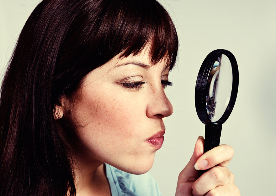 Woman peering through magnifying glass, looking suspicious