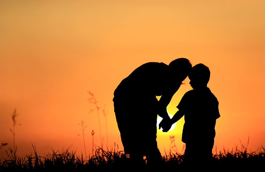 Parent talking to child, holding hands, silhouetted against sunset