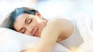 Woman sleeps face down on bed. Dressed in white.