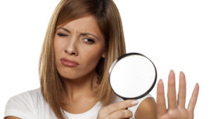 beautiful young woman analyzing her nails with a magnifying glass Pic: Istockphoto