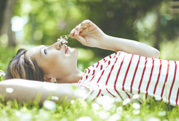 Lady lying on grass, smelling the flowers Pic: Istockphoto