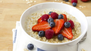 A bowl of healthy porridge with fresh berries and drizzled with honey.