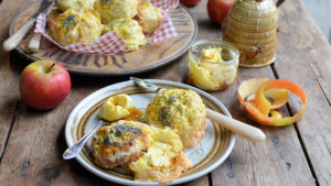 A plate of buttered scones on a rustic table with honey pot and apples