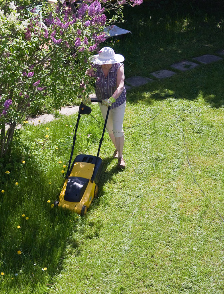 Woman mowing grass wearing white hat