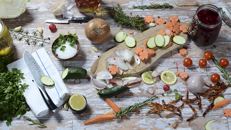 Wooden chopping board with onions, limes, carrots etc