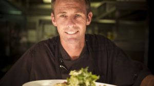 Head chef Garry Durrant with a plate of food topped with green leaves