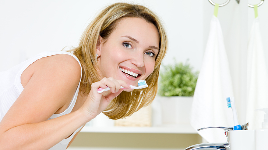 Young happy caucasian woman cleaning teeth with toothbrush in bathroom