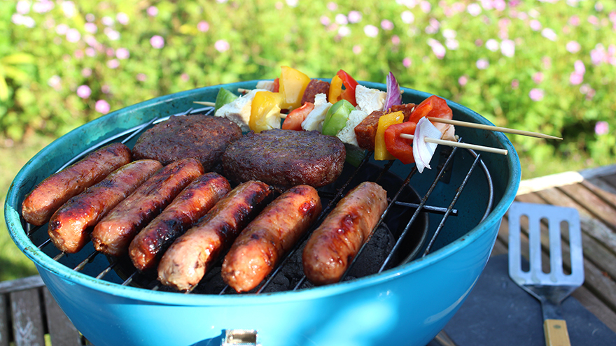 Photo showing a portable kettle barbecue / charcoal BBQ in a garden setting, stood on a wooden patio table with the lawn and pink hardy geraniums forming the blurred background. Pictured cooking on the barbecue are some sausages, beef burgers and colourful kebabs, made from red, green and yellow bell peppers, red onions and chicken pieces.
