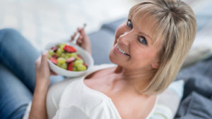 Woman eating bowl of berries and fruit
