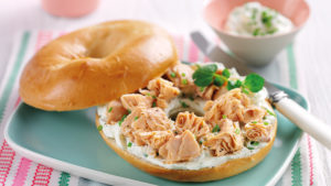 White bagel, lid removed, with cream cheese, salmon and watercress filling