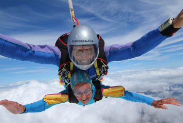 Alma Cater and skydiving partner smiling as they plunge through the sky