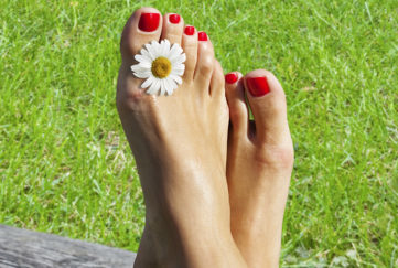 Woman's feet resting on a log, green grass behind, a daisy between two toes