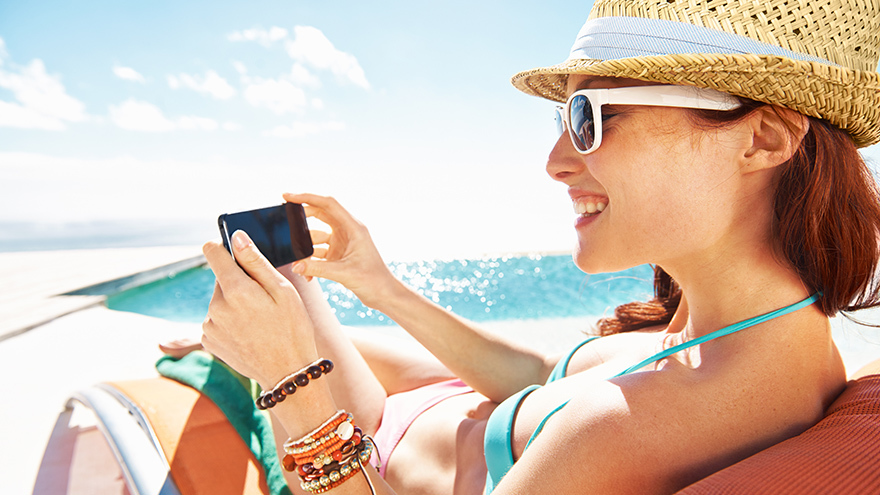 Lady on beach looking at mobile phone. Many phone cameras contain space tech Pic: Istockphoto
