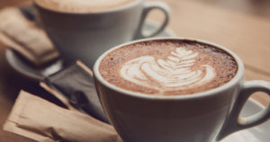 Two perfect cups of cappuccino on a wooden table, close-up.