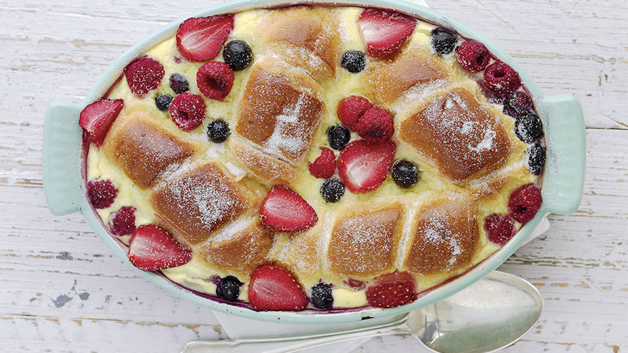 Oval pudding dish with scattered berries and golden brown pieces of sponge set in a custard-like sauce