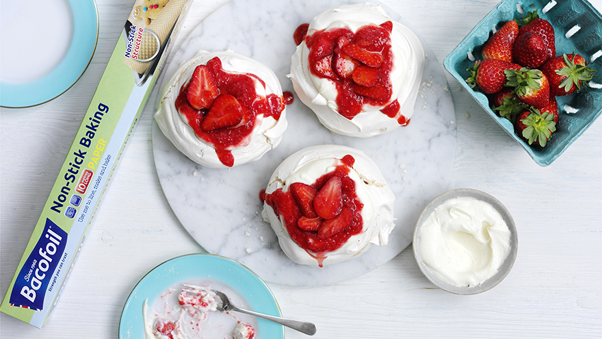 Three mini strawberry meringue pavlovas on a plate, a punnet of strawberries and a plate and spoon scraped clean