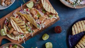 Fish tacos with salad and salsa on a chopping board with lime wedges