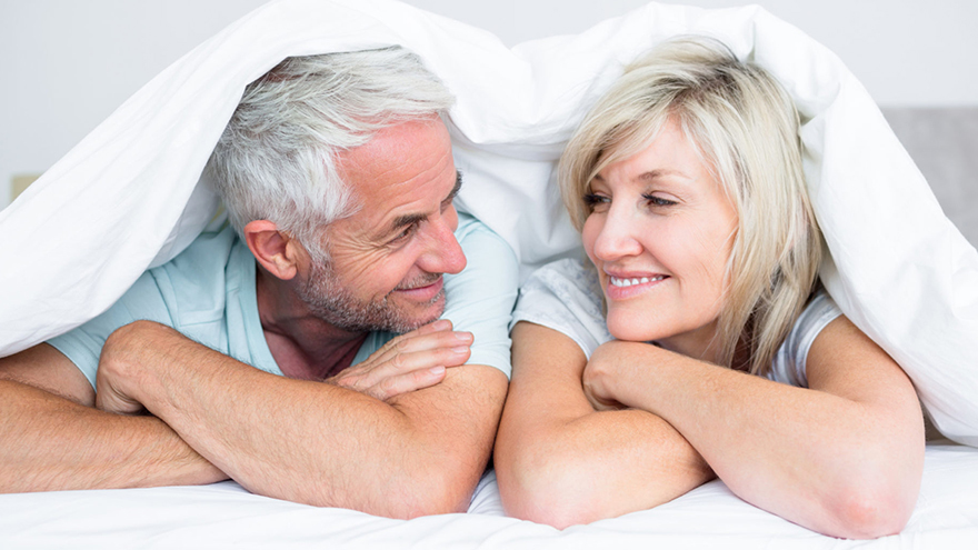 Mature couple in bed smiling at each other