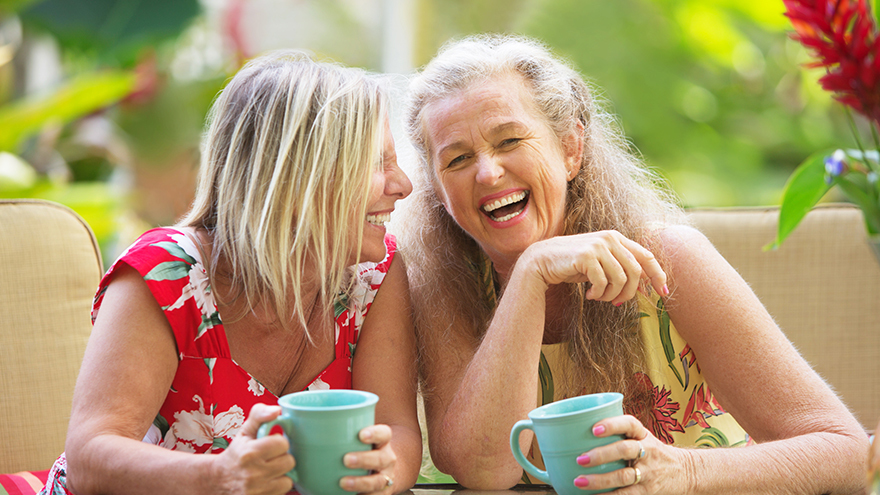 Two middle aged women with mugs of tea, laughing together