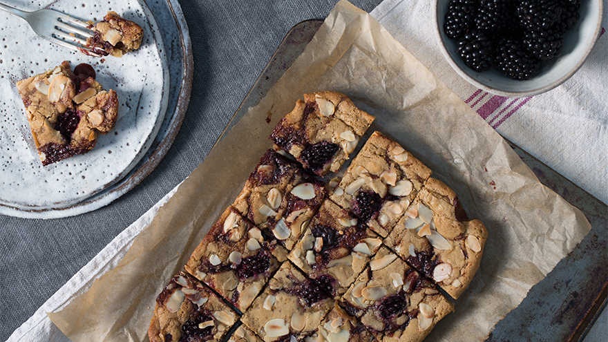 Blackberry blondies, frshly cut into squares. on baking paper with fresh ripe blackberries