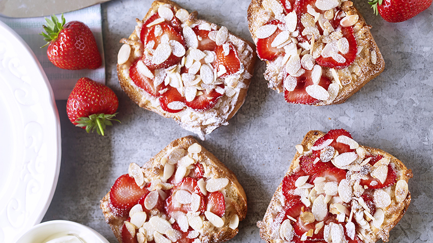Four slices of brioche bread topped with strawberries and almonds