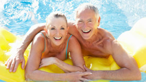 Senior couple having fun in pool outdoors smiling to camera