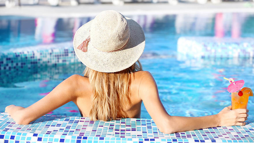 Woman in straw hat sitting in pool with cocktail. Her back is to the camera.