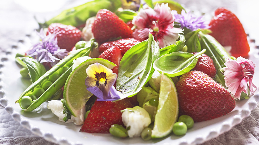 A plate of salad with strawberries, peas in an opened pod, goat's cheese and garnished with pansy flowers