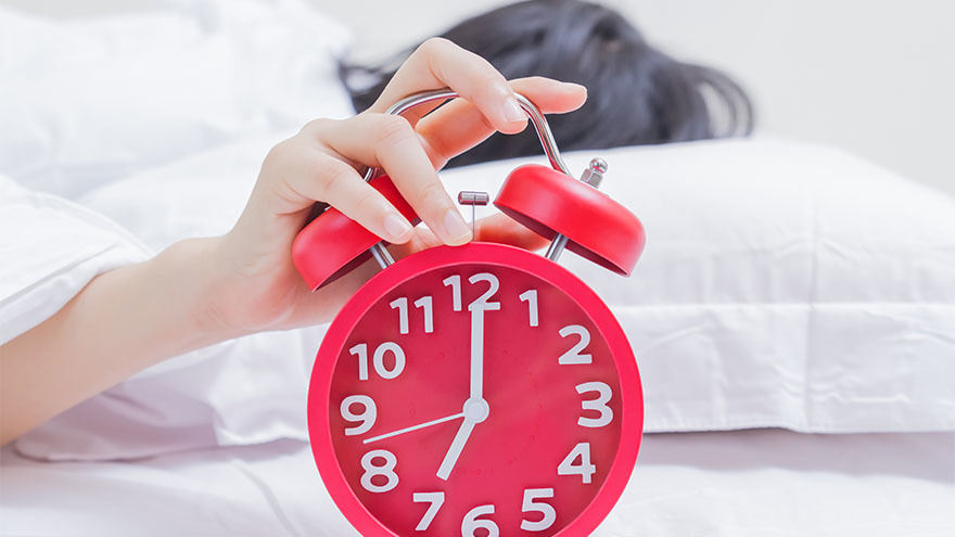 Red alarm clock showing 7am, woman reaching out from under duvet towards it