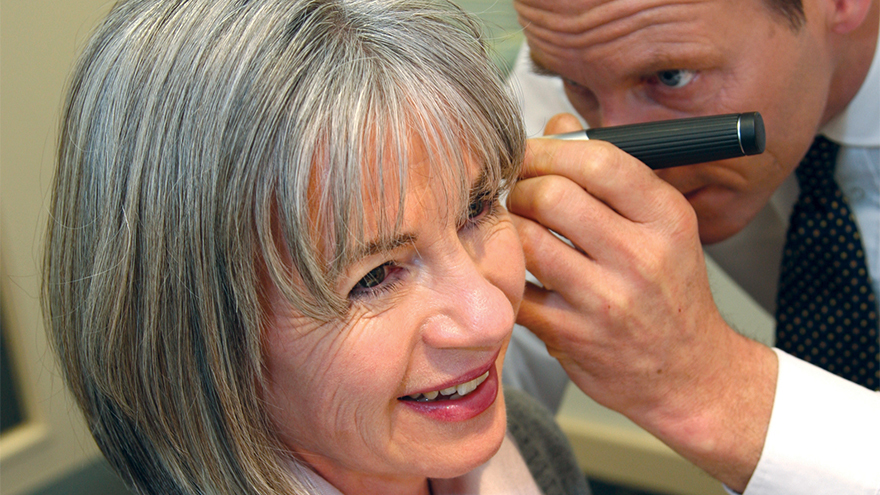Middle aged woman having her ear examined with a light